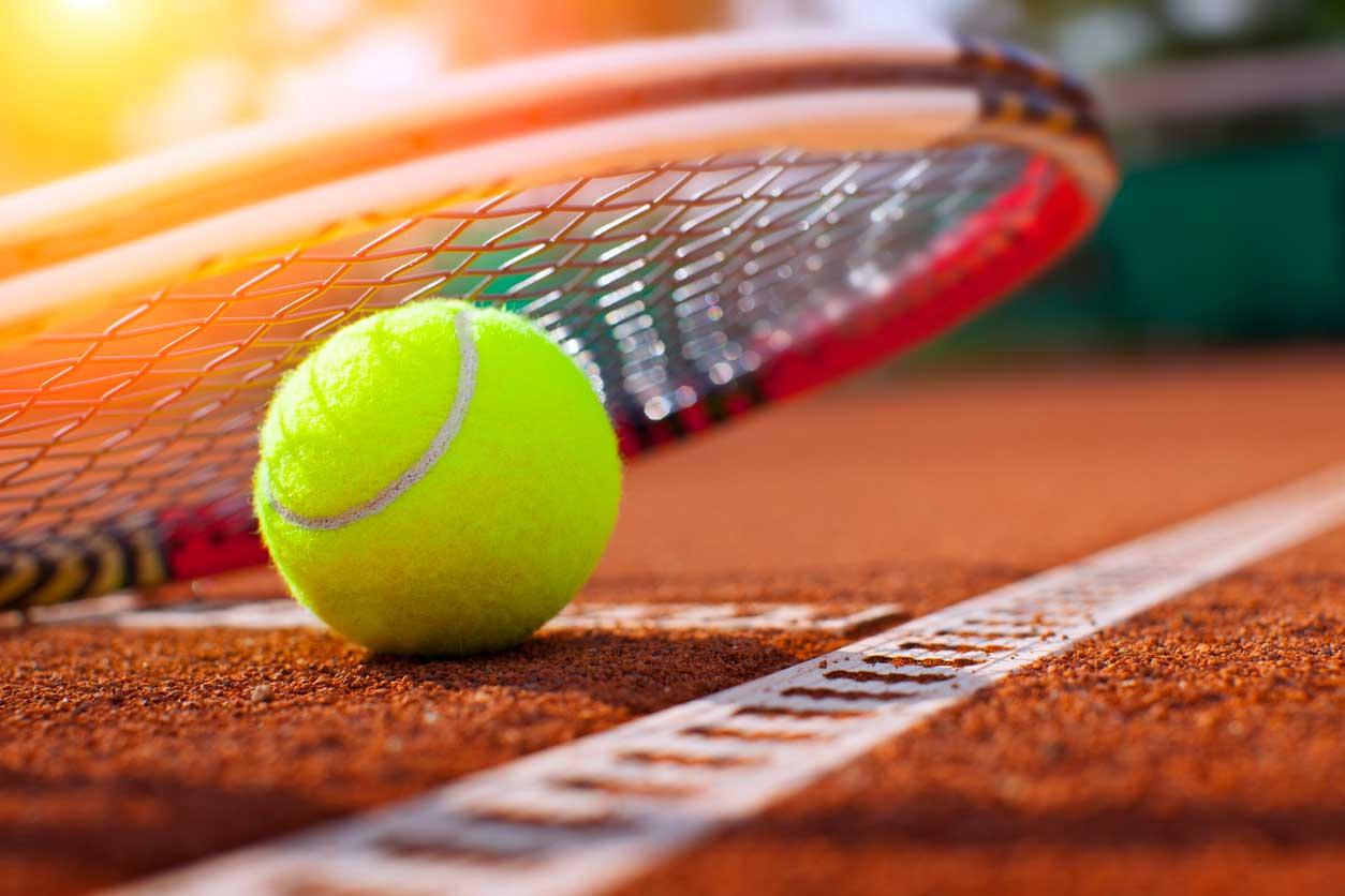 Tennisball auf dem Tennisplatz mit Tennisschläger