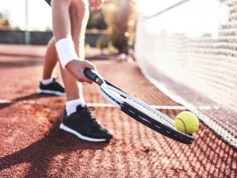 Tennisball wird vom Spieler aufgeschlagen