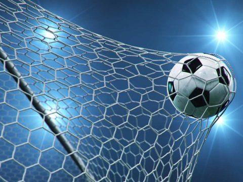 Torschuss beim Fußball vor Stadionbeleuchtung
